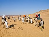 Aswan, Egypt - August 23: A Caravan Of Tourists In Camels Crossing The Nubian Desert On August 23, 2