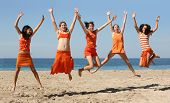 stock photo of beach party  - five girls in orange clothes jumping on the beach - JPG
