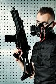 stock photo of skinhead  - Shot of a conceptual man in a respirator holding a gun - JPG