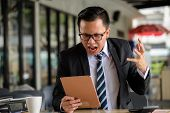 Angry Businessman See Bad News By Tablet poster