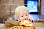 Cute Blonde Boy Eating Slice Of Pizza At Fast Food Restaurant poster