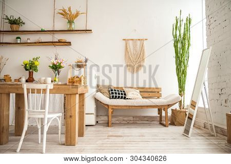 poster of Wooden Table In A Bright Rustic-style Kitchen. Scandinavian Style In The Interior Of The Kitchen.