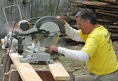 A carpenter using a chop saw
