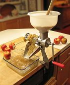 Applesauce being made using a strainer that separates the pulp from the skins