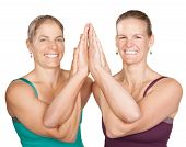 stock photo of namaskar  - Two smiling women perform entwined namaskar over white background - JPG