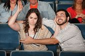 stock photo of pervert  - Angry woman hits man trying to grab her in theater - JPG