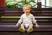 Cute Little Baby Sitting On Bench