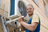 picture of air conditioner  - Young setup man installs the new air conditioner for office - JPG