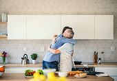 An Adult Hipster Son And Senior Father Indoors At Home, Hugging When Cooking. poster