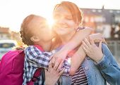 First Day At School. Mother Hugs Daughter In Sun Rays. Happy Smiling Family. Cheerful Teen Girl With poster