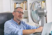 Man suffers from heat while working in the office and tries to cool off by the fan poster