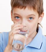 Child drinking water. Boy drinking water from a glass