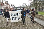 Occupy Exeter activist march out of the Cathedral grounds
