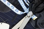 Still life photo of the inside of a bespoke suit jacket with hand stitching and scissors, tape measu