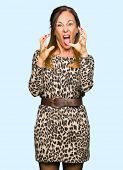 Beautiful middle age woman wearing leopard animal print dress Shouting frustrated with rage, hands t poster