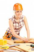 Female carpenter with helmet at work isolated on white background