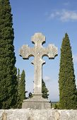 stock photo of crucifiction  - tombstone crosses on blue mediterranean sky with cypruses - JPG
