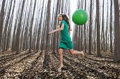 foto of vaquero  - Beautiful blonde girl dressed in green jumping into the woods with a balloon in Fuente Vaqueros Granada Spain - JPG