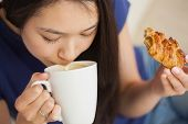 Young asian woman sipping her coffee and holding a pastry in living room at home