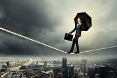 stock photo of roping  - Image of pretty businessman balancing on rope - JPG