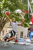 Man Attempts Slam Dunk During Outdoor Street Basketball Tournament