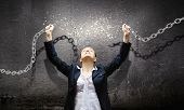 stock photo of slavery  - Image of businesswoman in anger breaking metal chain - JPG