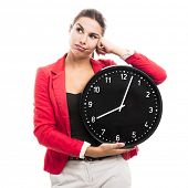 Bored business woman holding a big clock on the hands