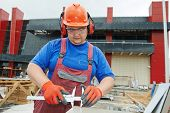 image of millwright  - Builder worker with caliper measure plastic parts at construction site - JPG