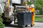stock photo of garbage bin  - urban municipal recycling garbage collector truck loading waste and trash bin - JPG