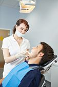 Male patient at dental examination with female dentist