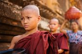 stock photo of southeast  - Southeast Asian young Buddhist monks walking morning alms in Old Bagan - JPG