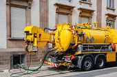 stock photo of jumpsuits  - Sewerage truck on street working  - JPG
