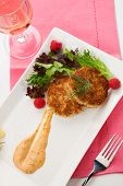 foto of crab-cakes  - Two crab cakes appetizer garnished with spicy sauce green salad and raspbery - JPG