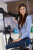 Portrait of beautiful photographer in studio, holding camera, smiling,