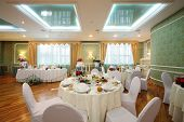 Beautiful hall with tables in a restaurant decorated for a wedding celebration