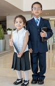 Young children in business clothes in the business center with communication devices, vertical photo