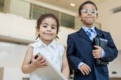 Little boy and girl in business clothes in the business center with communication devices, focus on