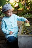pic of wet pants  - Little four year old boy in a blue outfit playing with paper boats in a small outdoor water fountain - JPG