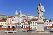 Lisbon, Portugal, February 01, 2013: The popular Portas do Sol Belvedere with St. Vicente Statue, Sao Vicente de Fora Monastery and Alfama rooftops