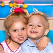 Closeup portrait of two cheerful child hugging each other, adorable siblings, smiling faces, best fr