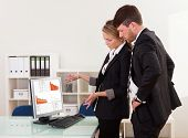 picture of unexplained  - Two professional young business colleagues stand in an office looking at a computer with dropping descending graphs - JPG