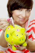 Young Woman Gives Money To Decorative Ceramic Piggy Bank