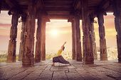 image of namaskar  - Woman doing yoga in ruined ancient temple with columns Hampi Karnataka India - JPG