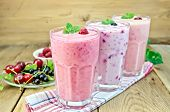 stock photo of buttermilk  - Milkshakes with black currant cherry raspberry in glass on the background of wooden boards - JPG