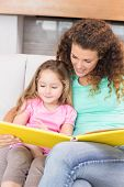 Pretty mother helping her little daughter read a storybook at home in living room