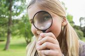 Close-up portrait of a cute young girl looking through magnifying glass at the park