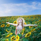 Beautiful happy young woman on the sunflower field under summer sky with freedom emotions