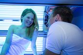 Employee In A Solarium Counseling Customer Or Client At Tanning Bed