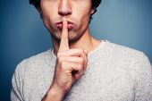 stock photo of taboo  - Young Man Gesturing Hush With Finger On Lips - JPG