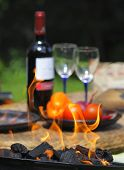 stock photo of ember  - Grill party preparation wine bottle with glasses on background - JPG